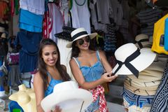 Deux touristes de femmes achetant le chapeau sur le marché en plein air ouvert d'Asiatique de jeunes achats femelles de vêtements Images libres de droits