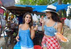 Deux touristes de femmes mangent les rues de marche de sourire heureuses de fruits frais dans de jeunes filles attirantes de vill Photo libre de droits