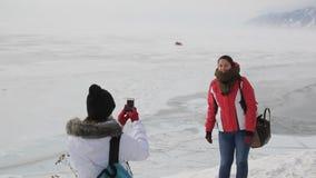 Deux touristes de femmes sont photographiées sur un fond des lacs et des montagnes glacials banque de vidéos