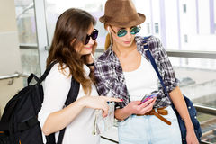 Deux touristes de jeunes femmes regardant la carte et la carte sont dans le terminal Image libre de droits