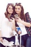 Deux touristes de jeunes femmes tenant un passeport et font le terminal de selfie Photographie stock