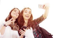 Deux touristes de jeunes femmes tenant un passeport et font le terminal de selfie Image libre de droits