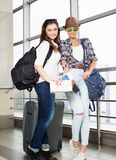 Deux touristes de jeunes femmes tenant une carte et un passeport et regardant l'appareil-photo Image stock