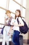 Deux touristes de jeunes femmes tenant une carte et un passeport et regardant l'appareil-photo Photographie stock libre de droits