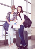 Deux touristes de jeunes femmes tenant une carte et un passeport et regardant l'appareil-photo Photos libres de droits