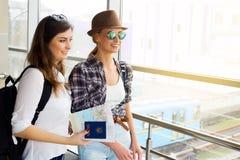 Deux touristes de jeunes femmes tenant une carte et un passeport et sont dans le terminal Photos libres de droits