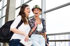 Deux touristes de jeunes femmes tenant une carte et un passeport et sont dans le terminal Photo stock