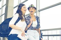 Deux touristes de jeunes femmes tenant une carte et un passeport et sont dans le terminal Image libre de droits