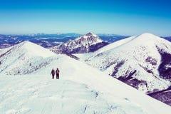 Deux touristes en voyage en montagnes neigeuses Image libre de droits