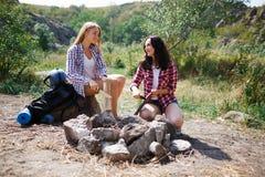 Deux touristes essayent de faire un feu pour faire cuire leur propre nourriture Les vacances d'été dans les amis de forêt sont al Photo stock