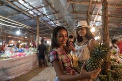 Deux touristes féminins choisissent l'ananas sur les jeunes femmes tropicales de marché en plein air achetant des fruits frais Photographie stock libre de droits