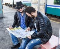 Deux touristes masculins d'amis reposent la recherche sur la carte Images stock