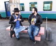 Deux touristes masculins d'amis s'asseyent et discutent Images stock
