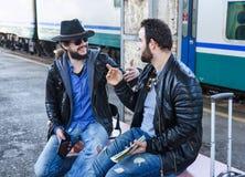 Deux touristes masculins d'amis s'asseyent et discutent Image libre de droits