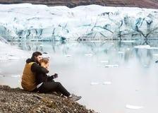 Deux touristes s'asseyent près de l'iceberg de glacier en Islande image stock