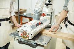 Deux tourneurs tenant la barre en bois sur la machine tambour-de meulage avec l'oscillation Photo stock