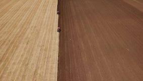 Deux tracteurs labourent la terre clips vidéos