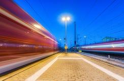 Deux trains à grande vitesse dans le mouvement sur la gare ferroviaire la nuit Image libre de droits