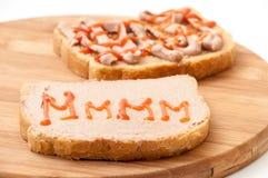 Deux tranches de pain ont enduit du pâté et du ketchup sur le conseil en bois photos libres de droits