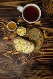 Deux tranches de pain, tasse de thé et une tasse de miel et de beurre, arachides et décoré des morceaux de pomme sèche se trouvan Photo stock