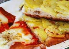 Deux tranches de pizza avec la tomate, le mozzarella et les pommes de terre photographie stock