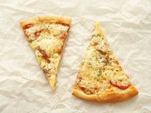 Deux tranches de pizza de pepperoni nouvellement fabriquée sur le parchemin de cuisson Fond de nourriture photo stock