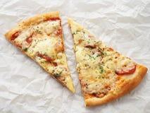 Deux tranches de pizza de pepperoni nouvellement fabriquée sur le parchemin de cuisson Fond de nourriture photos stock