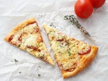 Deux tranches de pizza de pepperoni nouvellement fabriquée sur le parchemin de cuisson Fond de nourriture image libre de droits