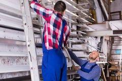 Deux travailleurs choisissant le profil de fenêtre de PVC Photo libre de droits