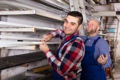 Deux travailleurs choisissant le profil de fenêtre de PVC Photographie stock libre de droits