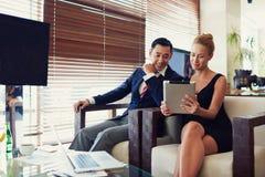 Deux travailleurs d'affaires emploient le comprimé numérique et le filet-livre au cours de la réunion en café image libre de droits