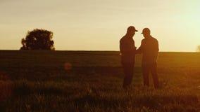 Deux travailleurs d'agriculteur communiquent dans le domaine, utilisent un comprimé Au beau coucher du soleil banque de vidéos