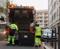 Deux travailleurs d'enlèvement des ordures chargeant des déchets dans le camion de rebut vidant des récipients image stock