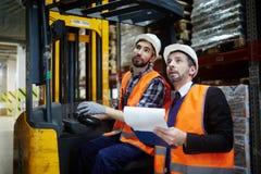 Deux travailleurs d'entrepôt montant le chariot élévateur  image stock
