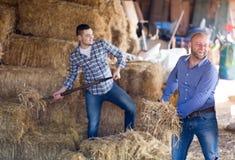 Deux travailleurs de ferme en grenier à foin Photos libres de droits