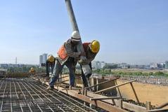 Deux travailleurs de la construction à l'aide du tuyau de la pompe concrète Photographie stock libre de droits