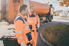 Deux travailleurs de service d'enlèvement de déchets ayant la petite pause image stock