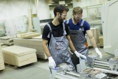 Deux travailleurs de sexe masculin travaillant dans l'industrie du meuble et créant le cust images stock