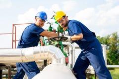 Deux travailleurs pétrochimiques inspectant des soupapes de refoulement sur un réservoir de carburant photos stock