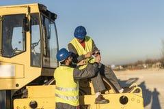 Deux travailleurs parlant dans la pause sur le bouteur de rouleau compresseur vehic photographie stock