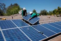 Deux travailleurs solaires de sexe masculin installent les panneaux solaires Images libres de droits