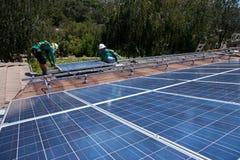 Deux travailleurs solaires de sexe masculin installent les panneaux solaires Image libre de droits