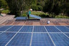 Deux travailleurs solaires de sexe masculin installent les panneaux solaires Photographie stock libre de droits