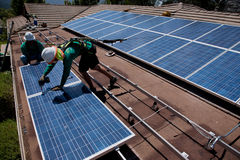 Deux travailleurs solaires de sexe masculin installent les panneaux solaires Photos stock