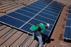 Deux travailleurs solaires de sexe masculin installent les panneaux solaires Image stock