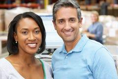 Deux travailleurs sur le terminal d'ordinateur dans l'entrepôt de distribution photographie stock