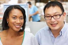 Deux travailleurs sur le terminal d'ordinateur dans l'entrepôt de distribution Photo stock