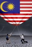Deux travailleurs tirant en bas du drapeau malaisien Photographie stock