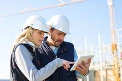 Deux travailleurs travaillant dehors avec un comprimé sur un chantier de construction Image stock