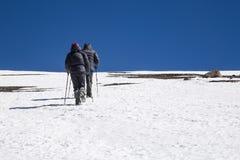 Deux trekkers allant au dessus de la pente couverte de neige Photo stock